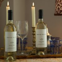 Forever Young Wine SB bottles near candle lit dinner