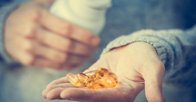 vitamins-vitamin-d-capsules-in-hand-of-man
