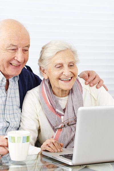 senior citizen couple using laptop computer